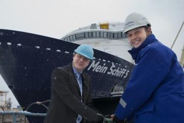 """Ferdinand Strohmeier y Jan Meyer accionan la válvula para inundar el dique que pondrá a flote el buque """"Mein Schiff 5"""". Nieva en el astillero de Turku"""
