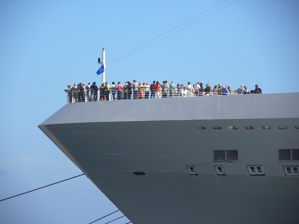 Un grupo de turistas presencian la salida desde la proa del buque