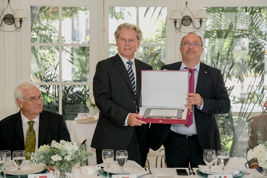 Javier Álvarez recibe una placa de manos del decano del Cuerpo Consular, Silvio Pelizzolo