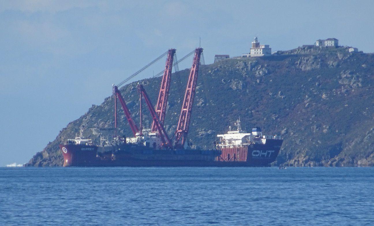 """El buque """"Osprey"""" y, al fondo, el faro de Finisterre"""