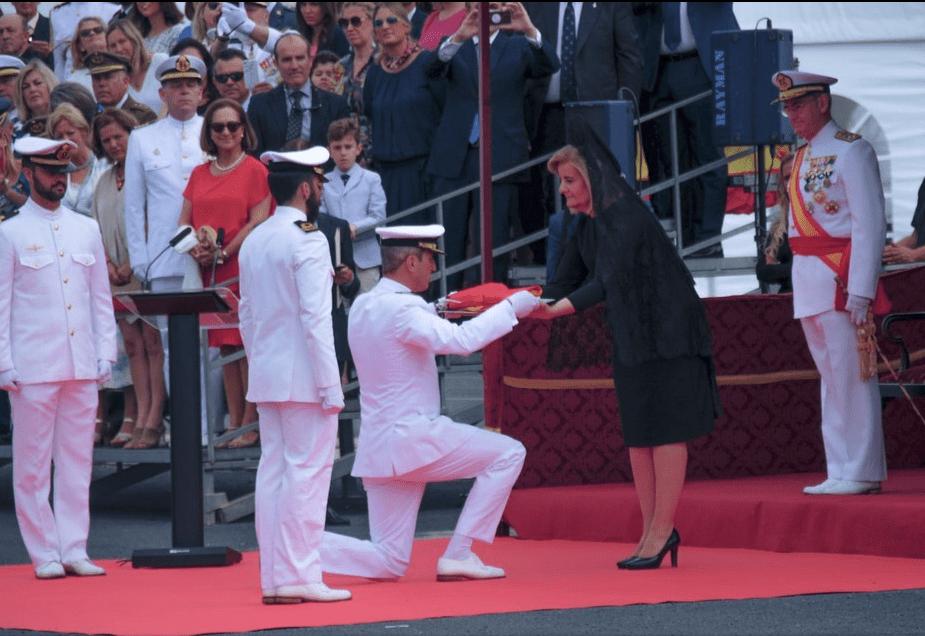 El comandante del buque recibe la bandera de combate de manos de la madrina