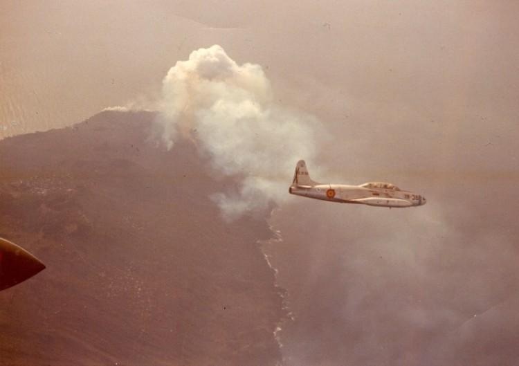Uno de los aviones Lockheed T-33A sobrevuela La Palma con el volcán en erupción