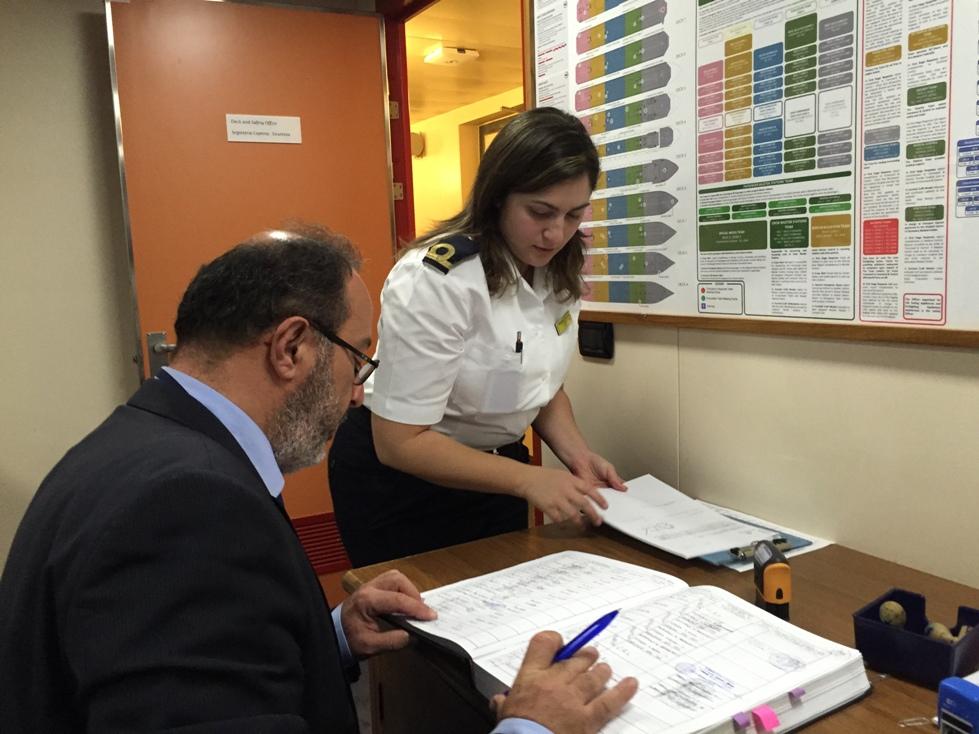 El cónsul de Italia supervisa la documentación que le presenta la oficial Gambino