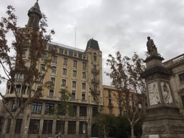 Monumento al marqués de Comillas en Barcelona. A la izquierda, la antigua sede de Compañía Trasmediterránea