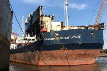 "La gabarra ""Spabunker Sesentayuno"", varada en la orilla, espera su desguace"