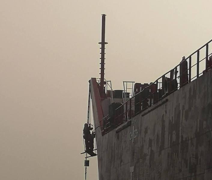 Un tripulante procede a pintar el nuevo nombre en la amura de babor