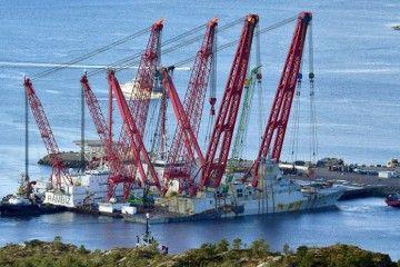 Dos potentes grúas sustentan el buque accidentado