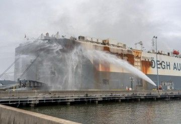 Los bomberos enfrían el costado de estribor del buque siniestrado