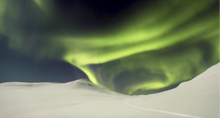 La aurora boreal ilumina el paisaje ártico de la larga noche de invierno en Finlandia