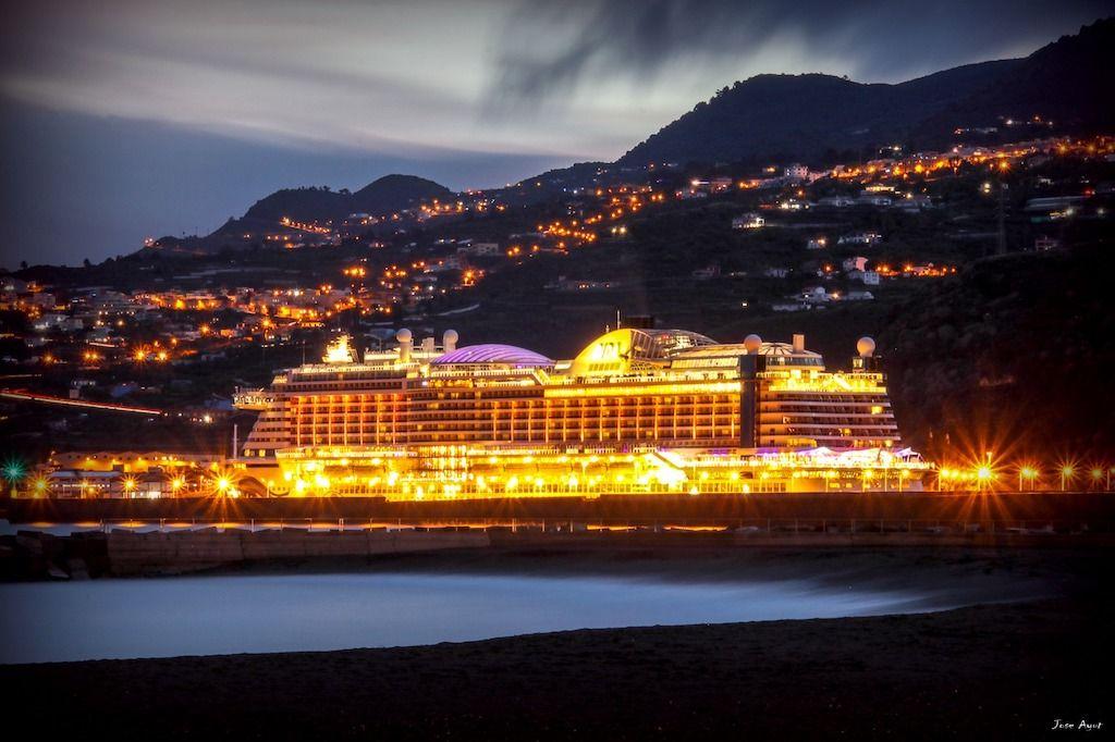 El buque destaca, iluminado, en el crepúsculo isleño