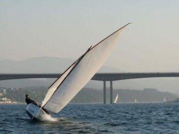 El capitán Iglesias Baniela gobierna un bote de vela latina en la ría del Eo