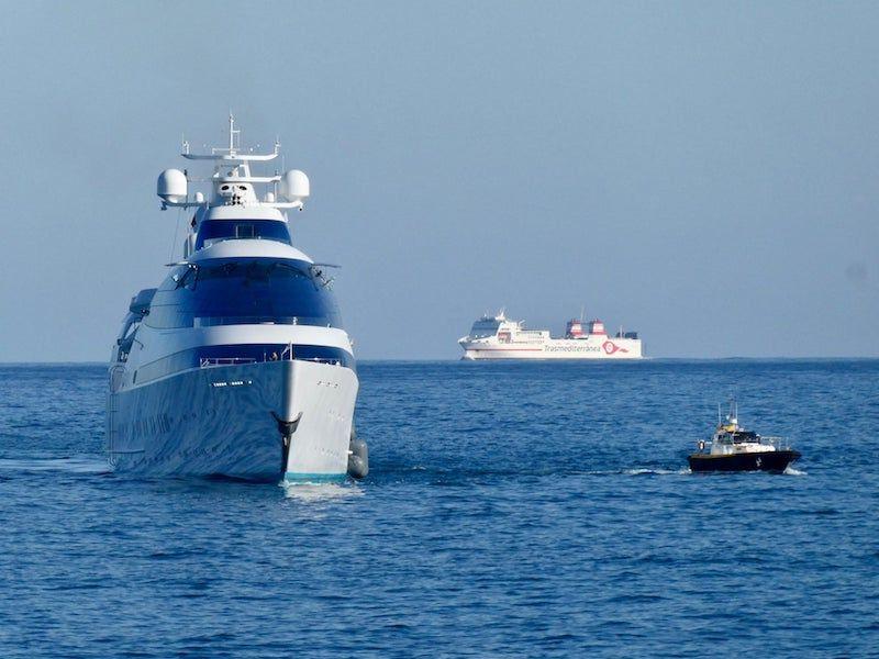 """Vista de proa del gigayate """"Yas"""". Al fondo, el ferry """"Ciudad de Ibiza"""""""