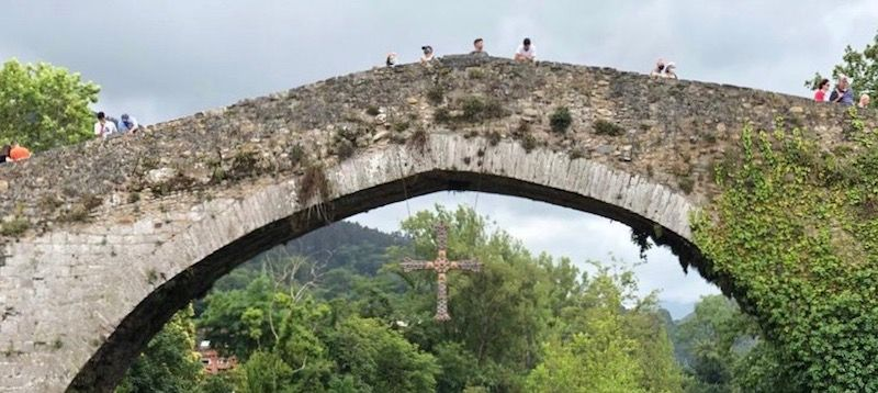 Una réplica de la Cruz de la Victoria pende del arco principal del puente